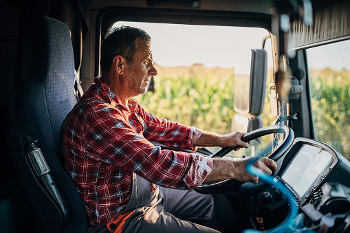 A male trucker driving a tractor-trailer