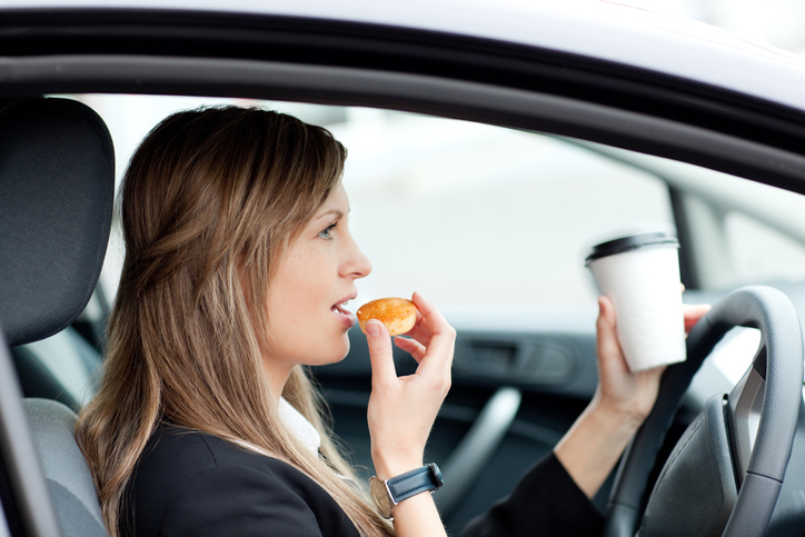 Woman eating and holding a to-go cup while driving.